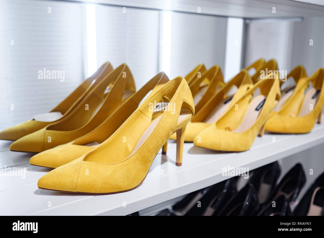 Trendy bright-colored shoes on shelf in shop - Stock Image