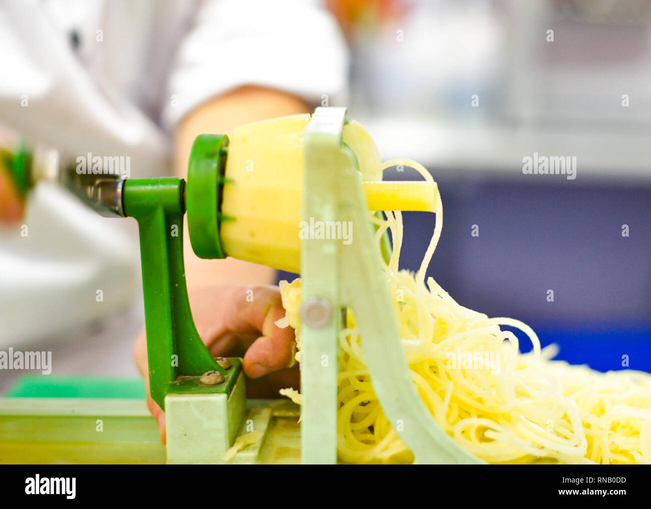 Vegetable Blade Spiralizer, Spiral vegetable slicer with potato spaghetti on table Stock Photo