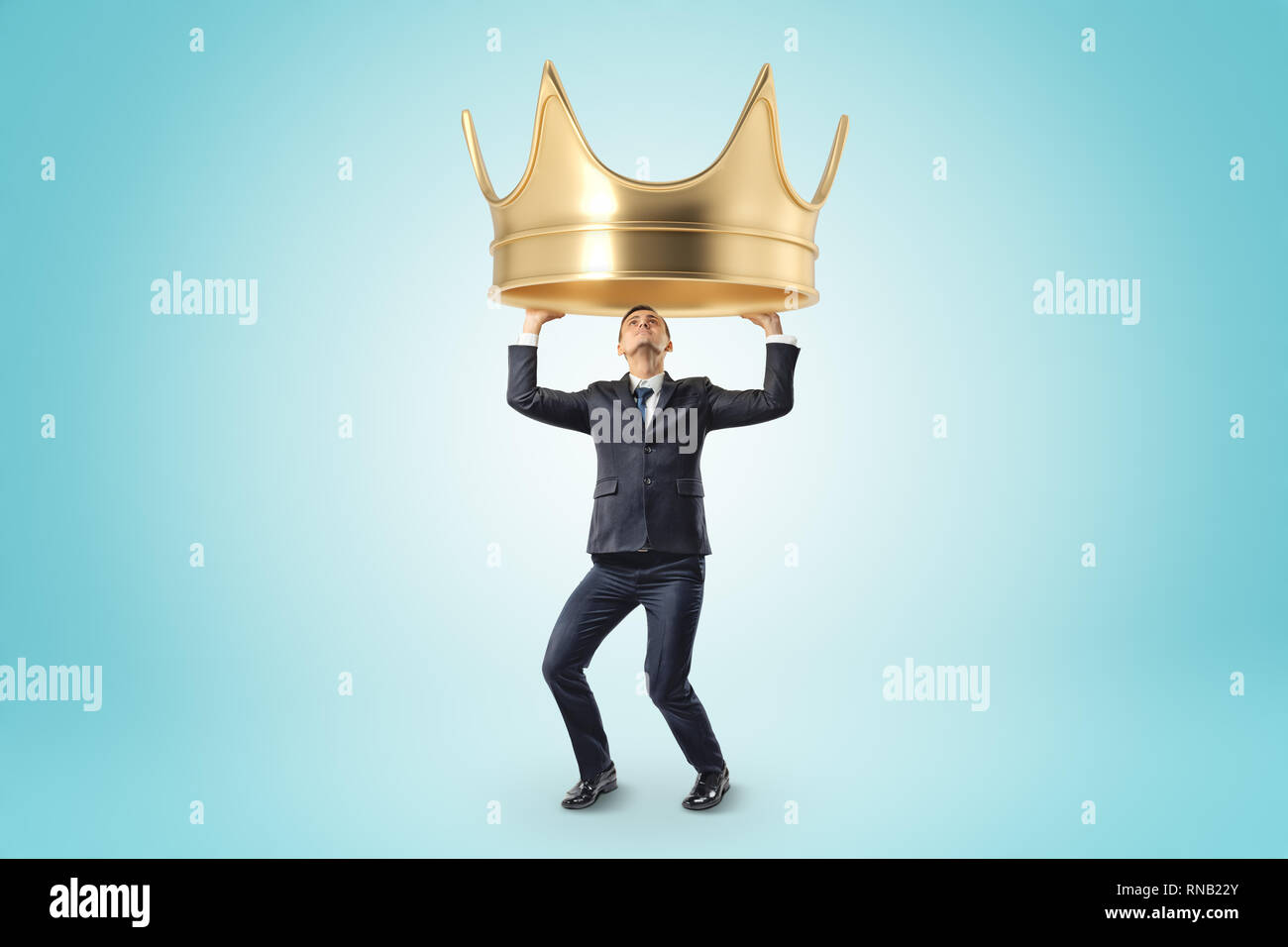 Young businessman holding heady golden crown above head on blue background - Stock Image