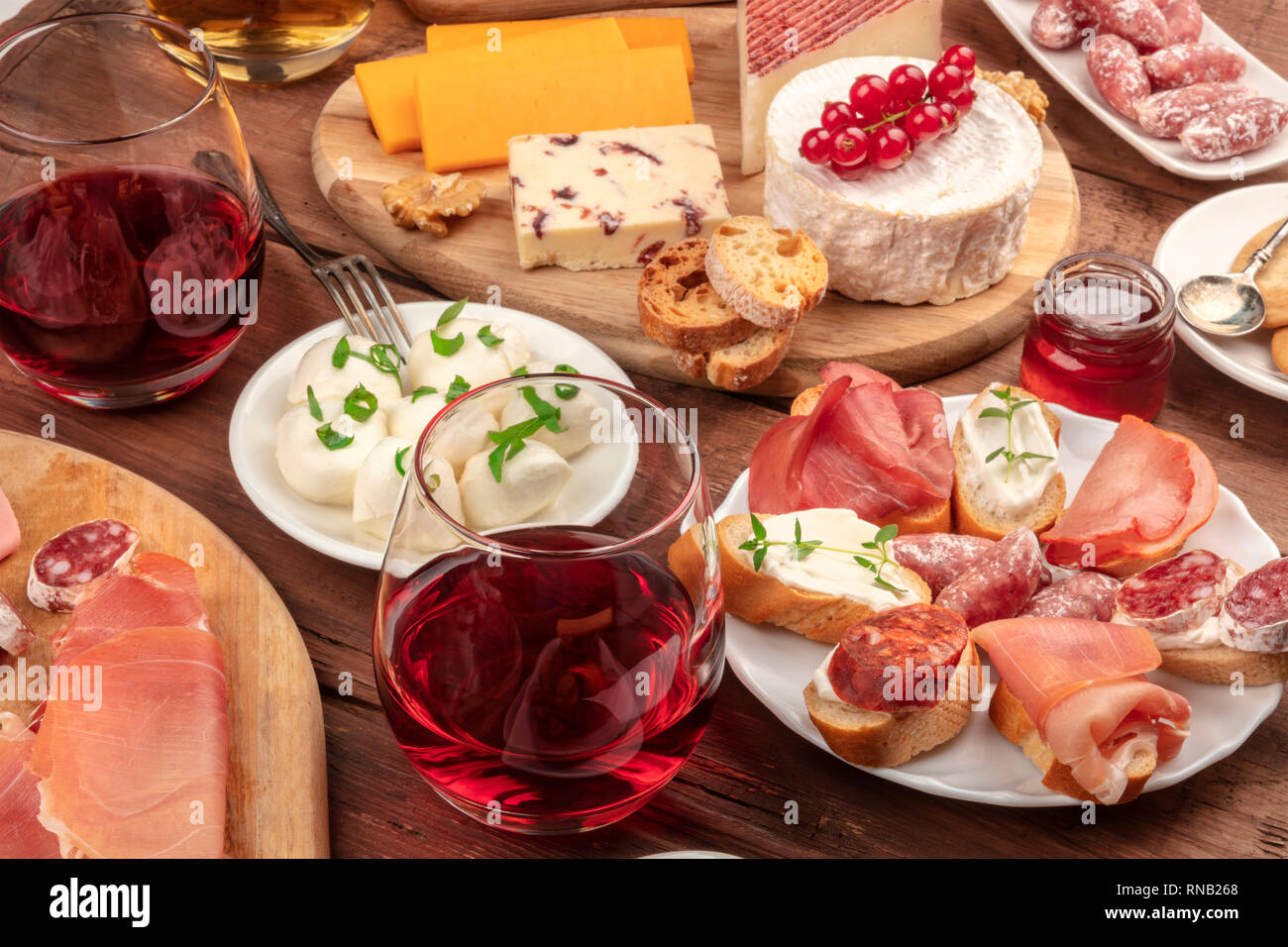 Wine tasting and pairing. A wineglass with sandwiches and a cheese platter on a dark wooden background - Stock Image