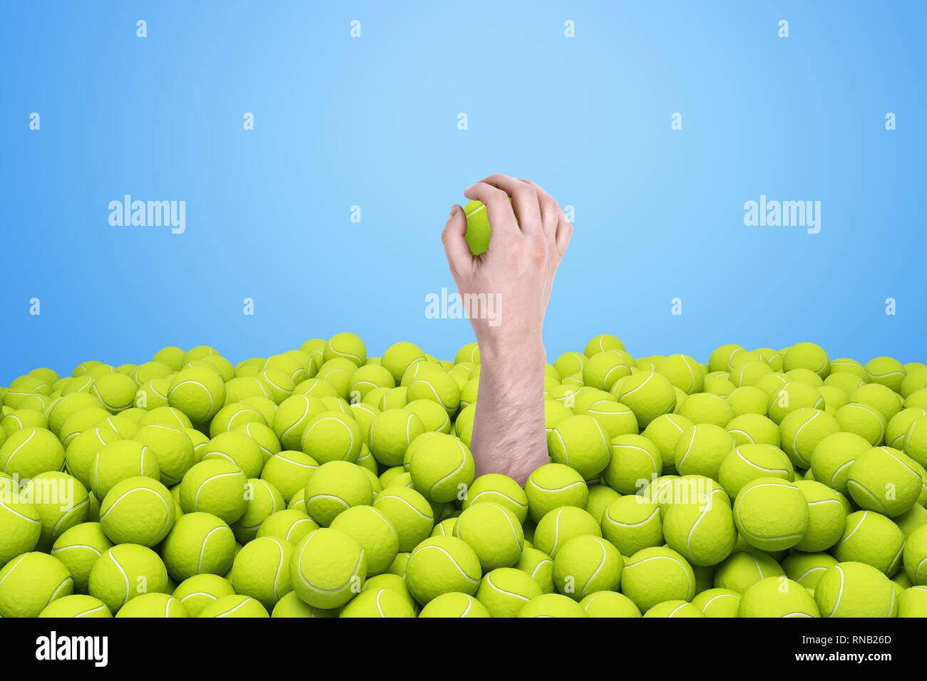 Hand appearing out of heap of yellow tennis balls holding one on blue background. - Stock Image
