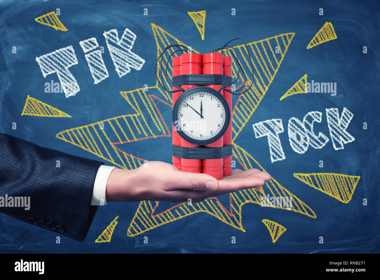 Man's hand facing up holding dynamite bundle with time bomb on blackboard background with chalk words 'tick tock'. - Stock Image