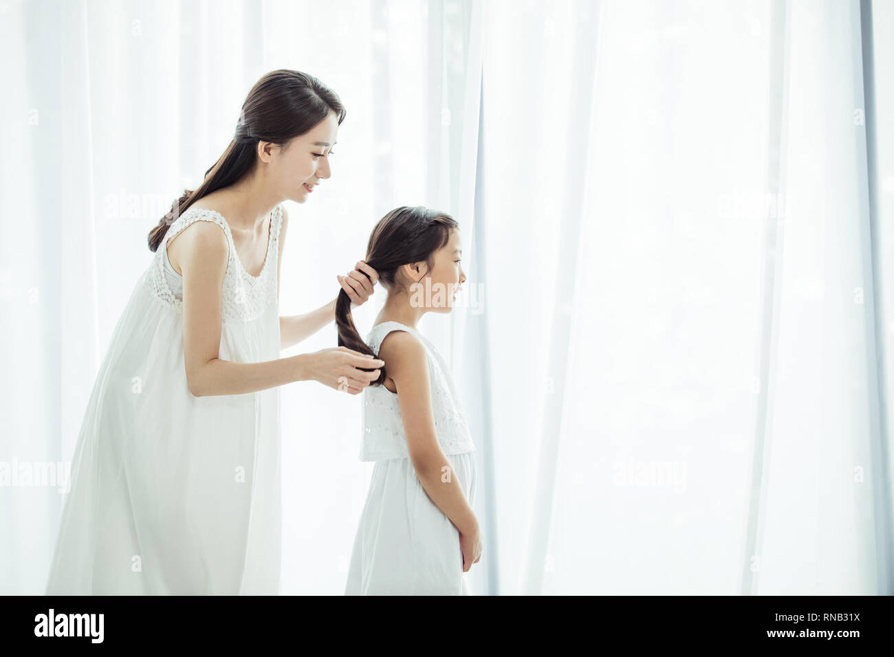 A mother who ties her daughter's hair - Stock Image