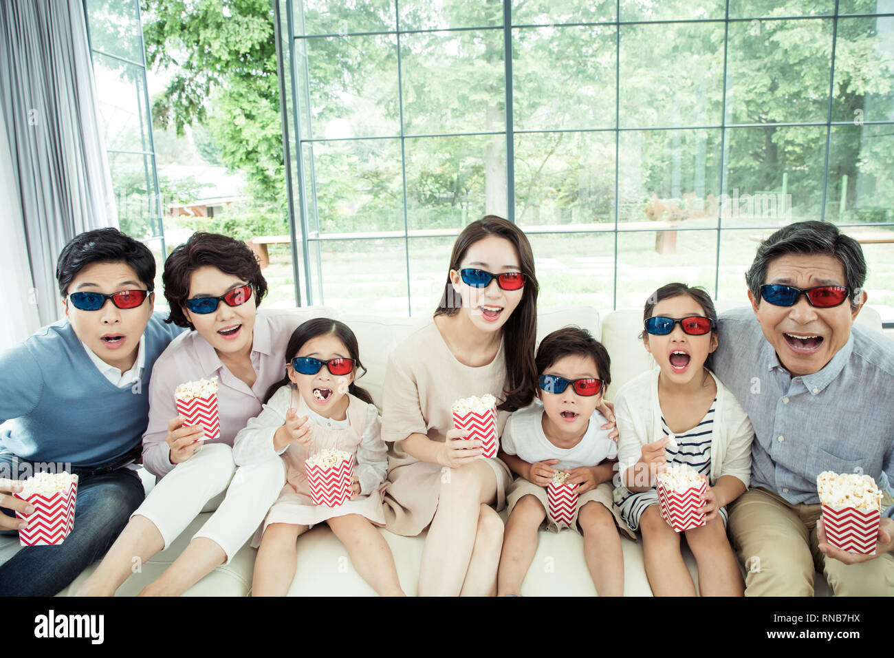 4a49e9d83b5 Third-generation family wearing 3d glasses and watching a movie ...