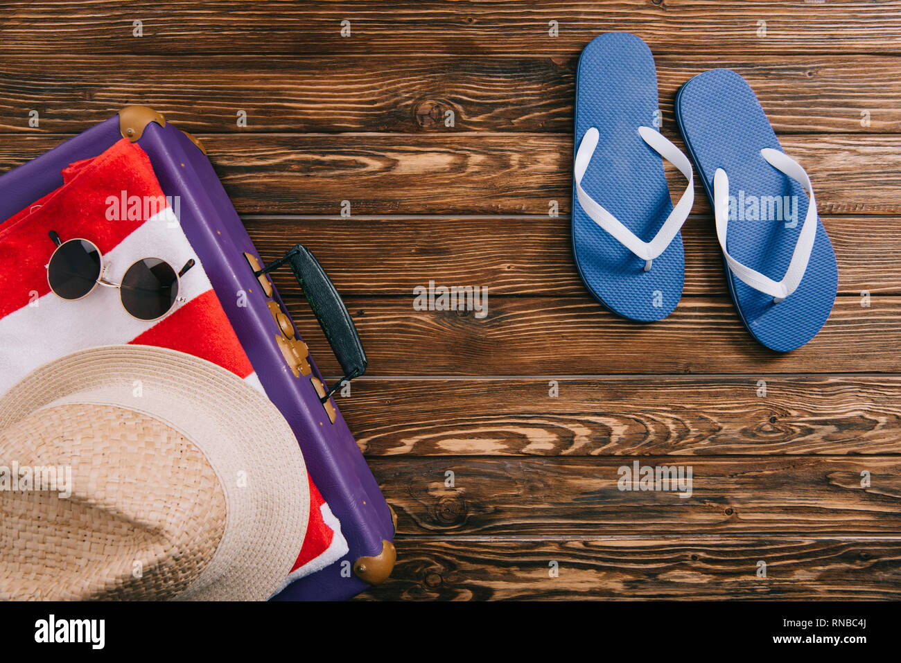 83621b22c top view of summer accessories and flip flops near suitcase on wooden  background - Stock Image