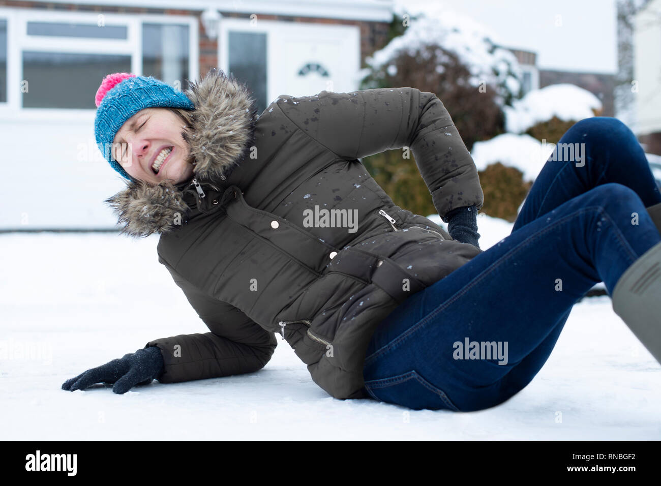 Woman In Pain Falling Over In Snowy On Slippery Street And Injuring Herself - Stock Image