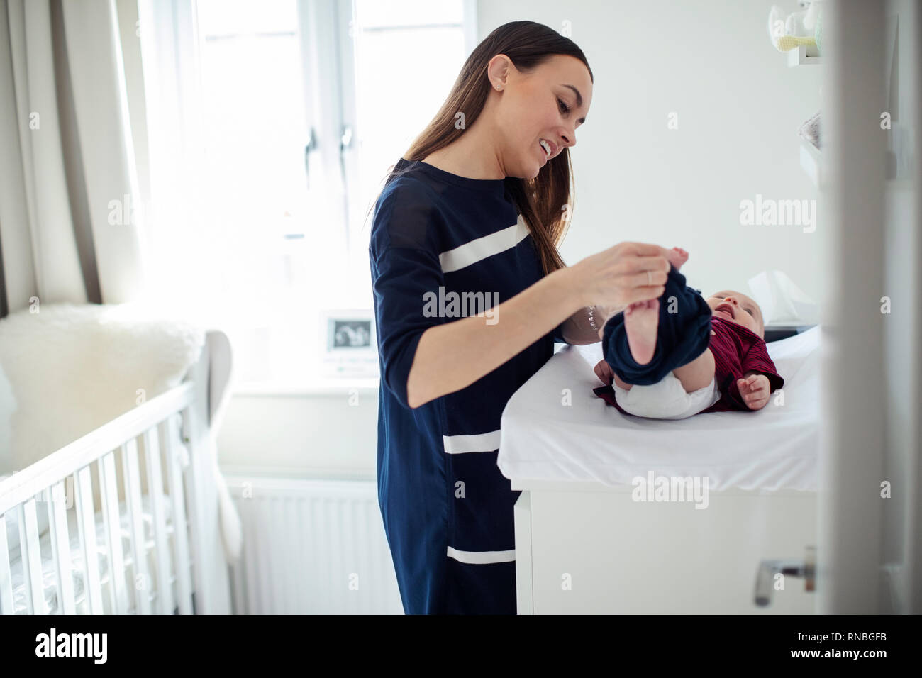 Mother In Nursery At Home Changing Baby Sons Daiper - Stock Image