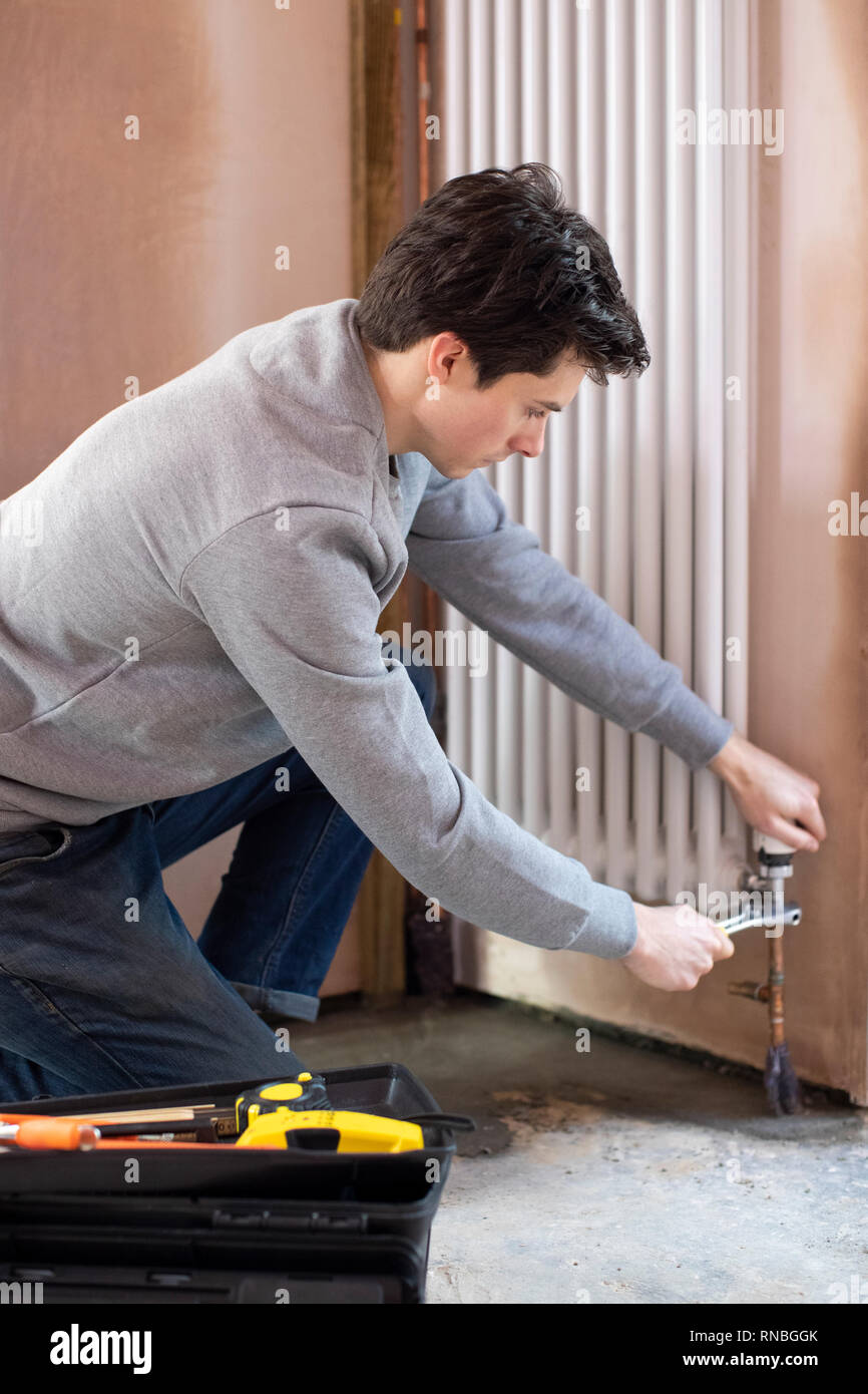 Male Plumber Fitting Vertical Radiator In Room Of House - Stock Image