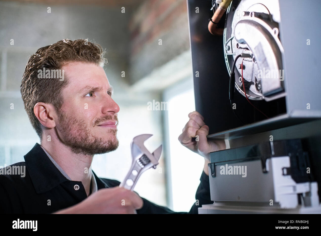 Male Heating Engineer With Adjustable Wrench Servicing Boiler - Stock Image