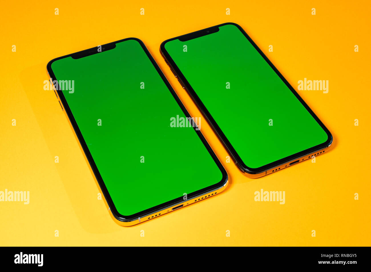 Green chroma key on on new mobile smartphne as hero object on bright glamorous modern neon pop orange background - smartphone ready to insert your app - Stock Image