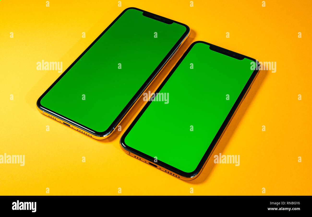 Green chroma key on new mobile smartphne as hero object on bright glamorous modern neon pop orange background - smartphone ready to insert your app - Stock Image