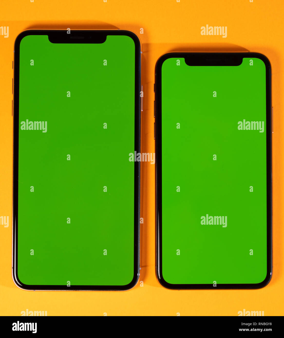 Green chroma key screen on new mobile smartphne hero object on bright glamorous modern neon pop orange background - smartphone ready to insert your app - Stock Image