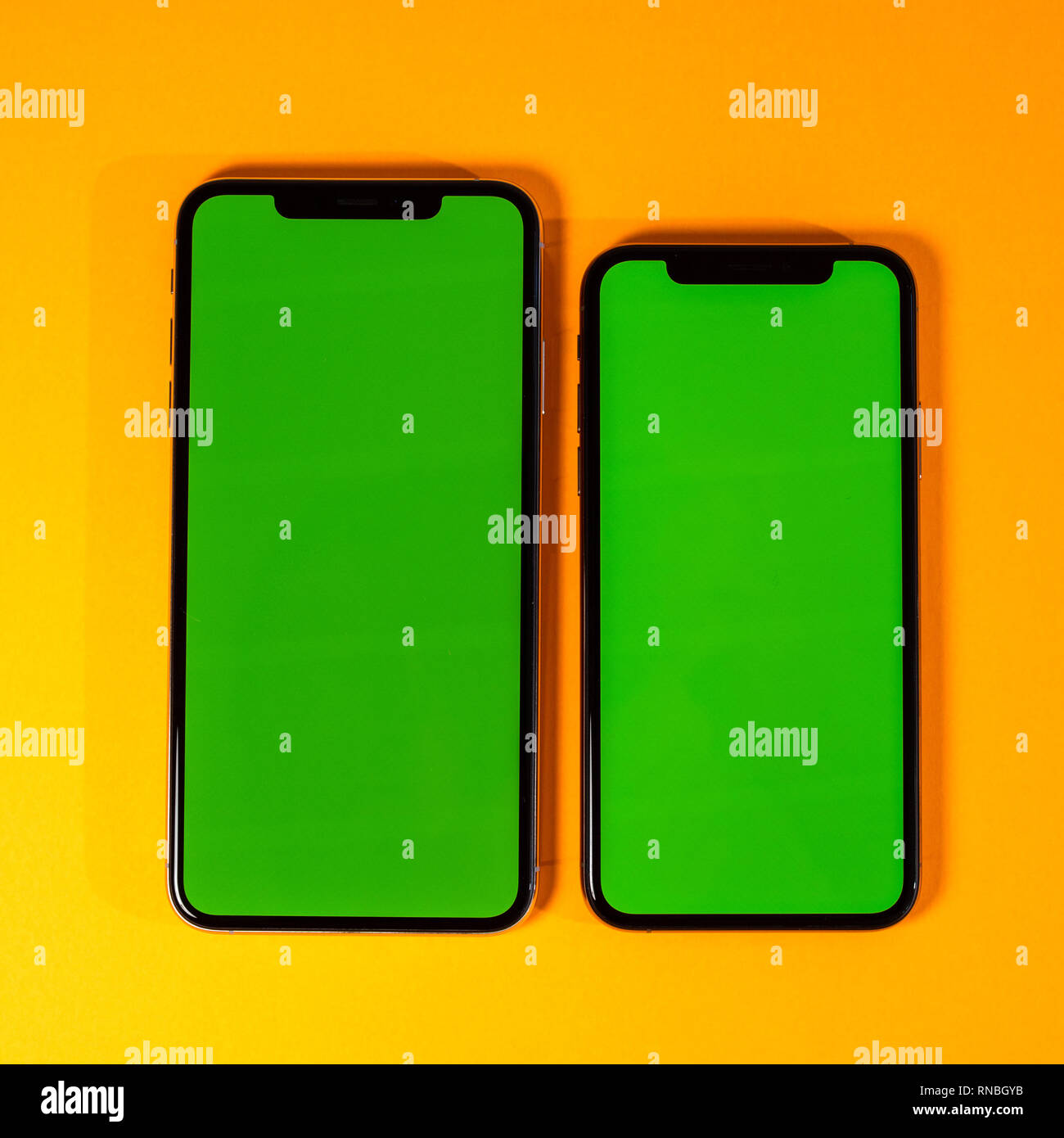 Green chroma key on new mobile smartphne as hero object on bright glamorous modern neon pop orange background - smartphone ready to insert your app square image - Stock Image