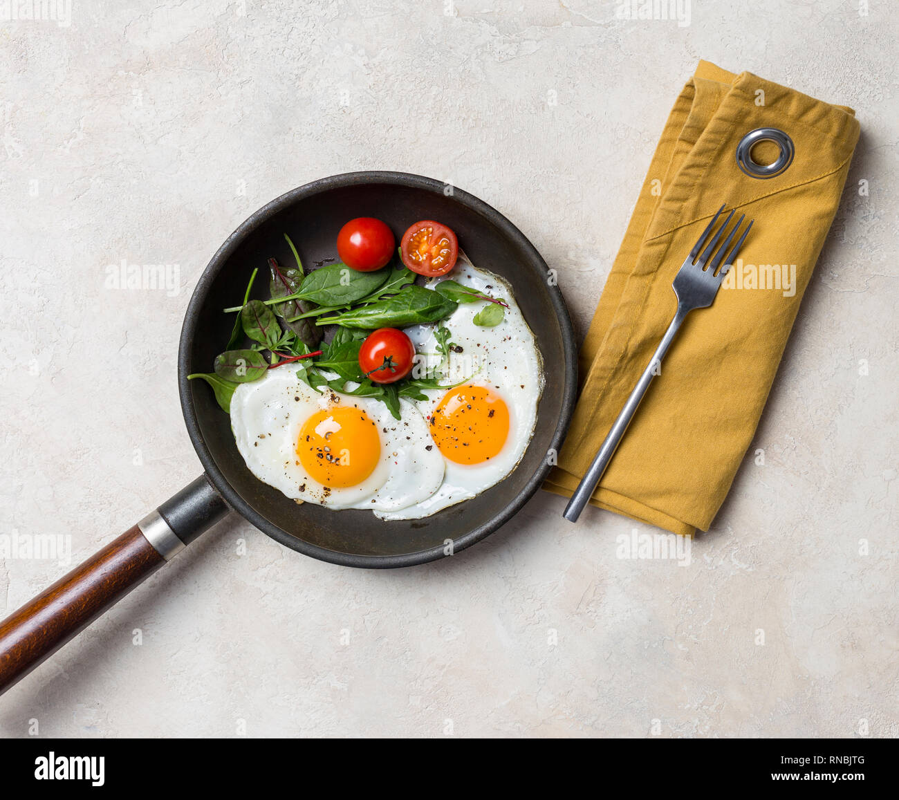 Skillet with two fried eggs, herbs, cherry tomatoes, fork and napkin at white background - Stock Image