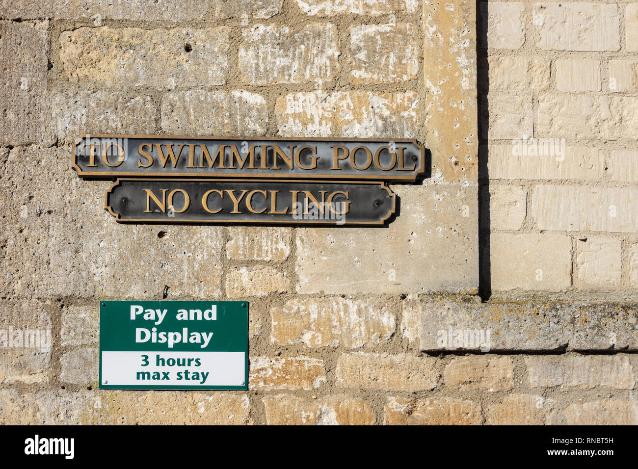 Wall showing edge of bricked up window with 3 signs fixed to it, Pay and Display, No Cycling, and To Swimming pool Stock Photo