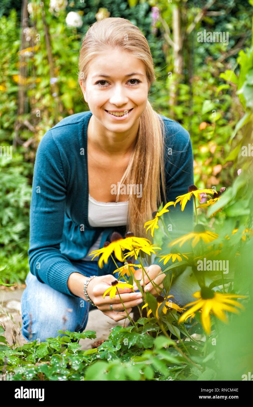 Junge Frau mit langen, blonden Haaren hockt vor einem Strauch Sonnenhueten / Rudbeckia im Garten. [(c) Dirk A. Friedrich - Stock Image