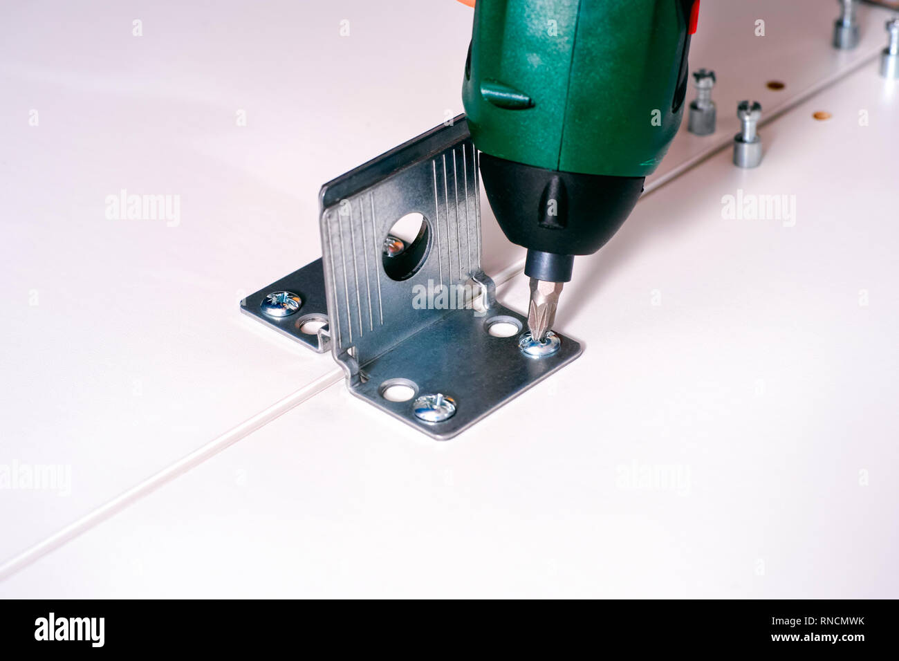 Screw drill twisting the screw into the furniture. Close-up. - Stock Image