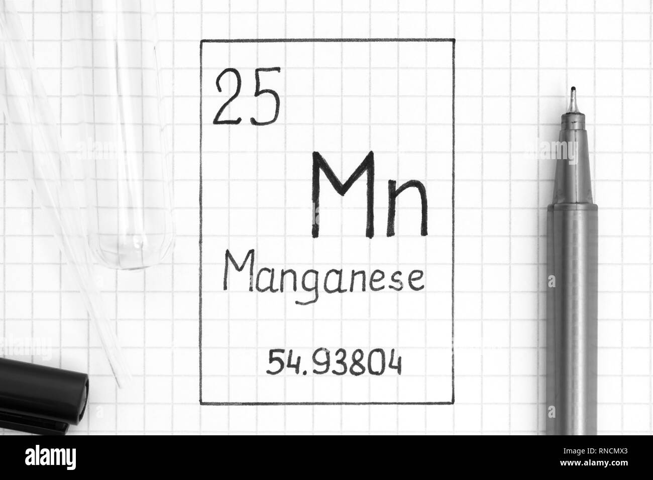 The Periodic table of elements. Handwriting chemical element Manganese Mn with black pen, test tube and pipette. Close-up. - Stock Image