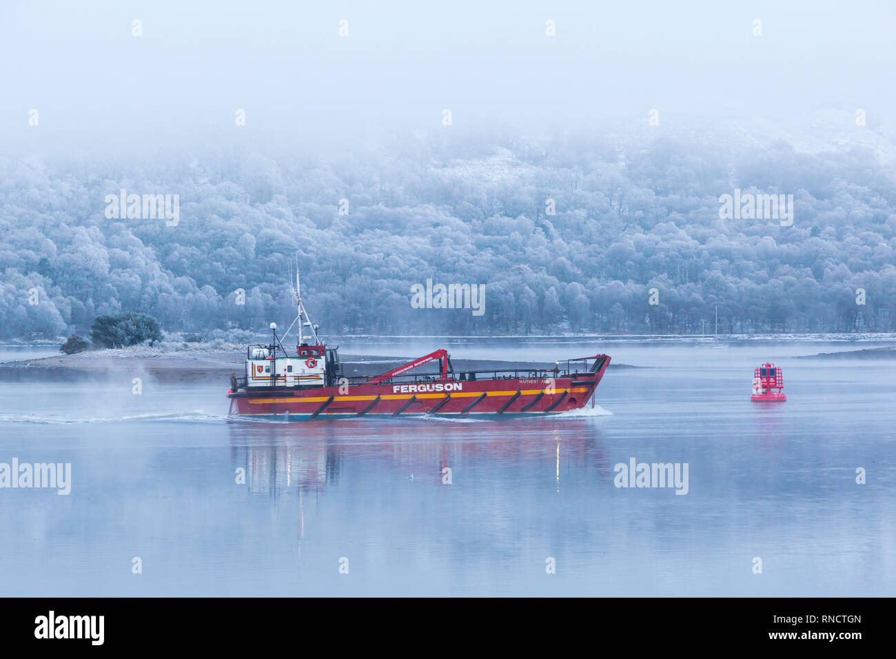 Ferguson transport & shipping vessel Harvest Anne motoring on a cold winter morning with frost and fog at Corpach, Fort William, Scotland in February Stock Photo