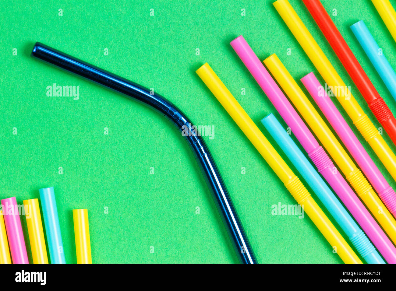 Stainless steel reusable drinking straw with plastic straws on green background - Stock Image