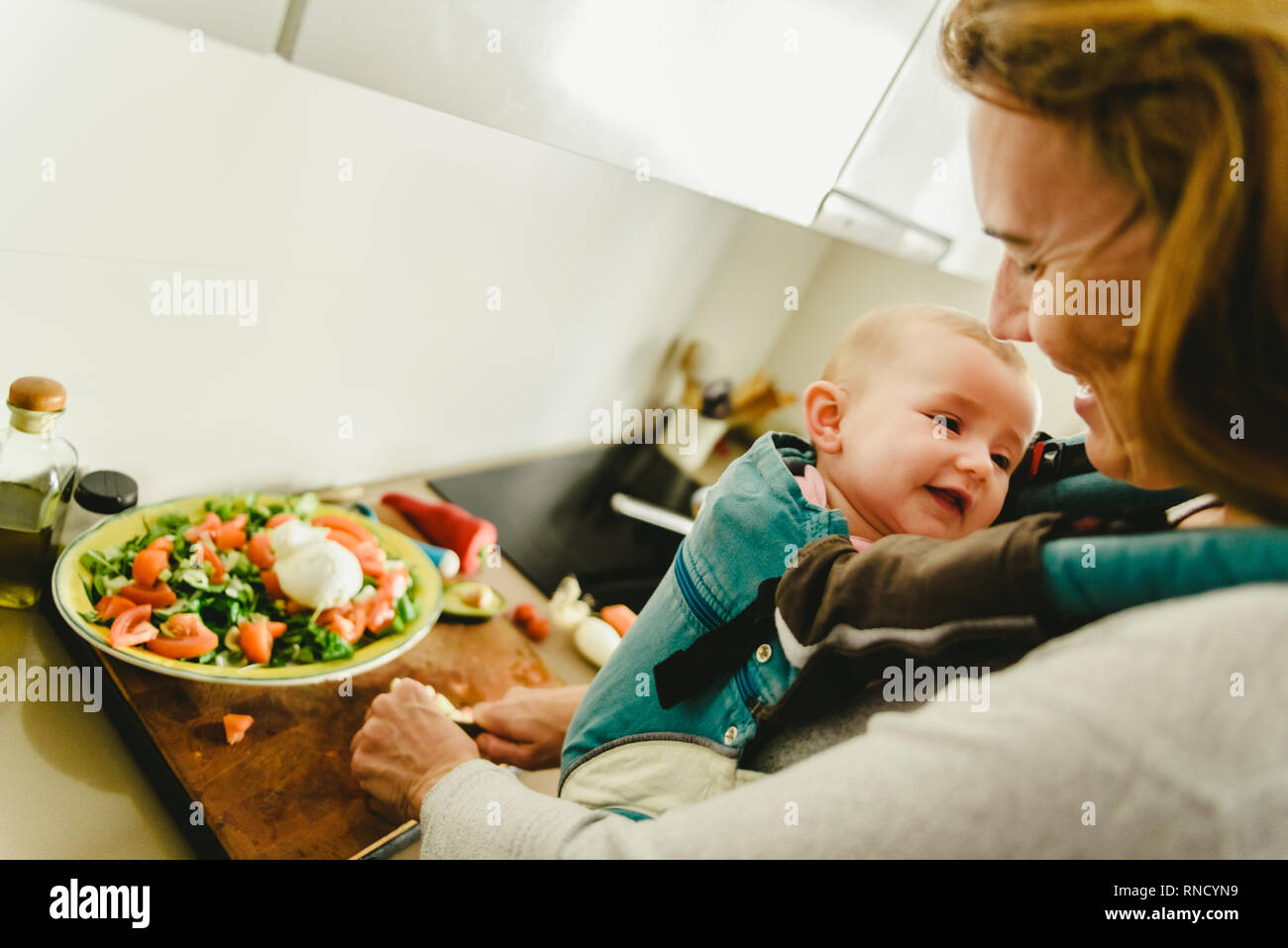 63c08d3a4f6 Smiling baby ported in baby carrier backpack looking at his mother while  she cooks