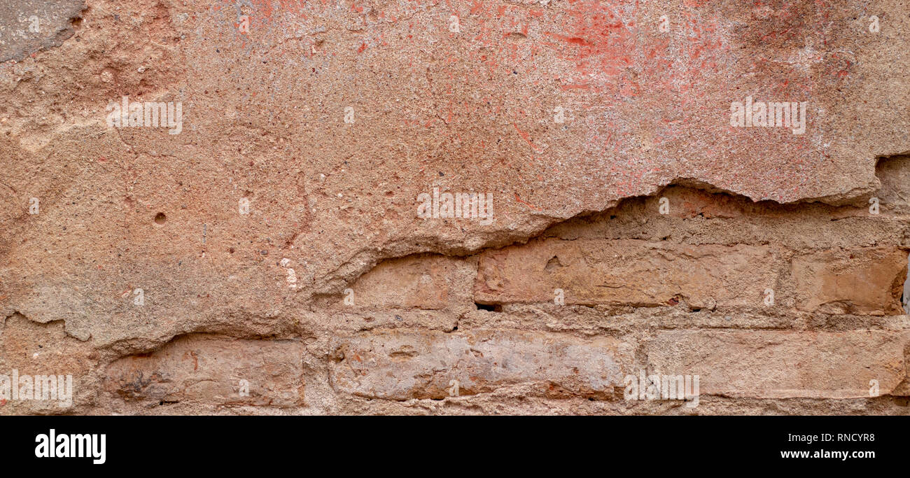 Old brick wall with peel stucco texture. Retro vintage worn wall background. Decayed cracked rough abstract wall surface Stock Photo