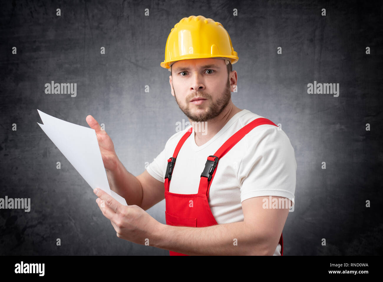 Angry construction worker holding papers - Stock Image