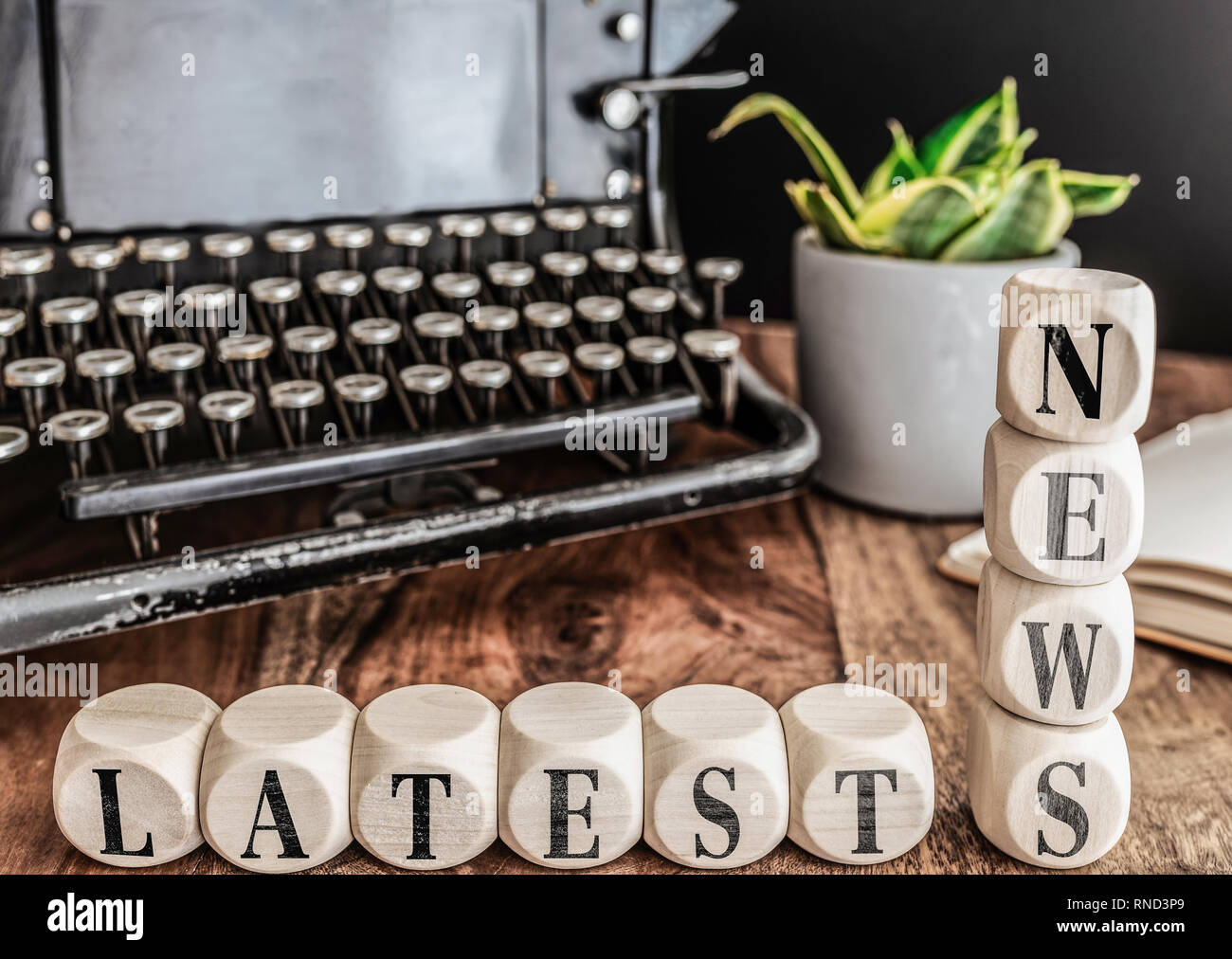 words LATEST NEWS on wooden blocks with vintage typewriter and potted plant in background - Stock Image