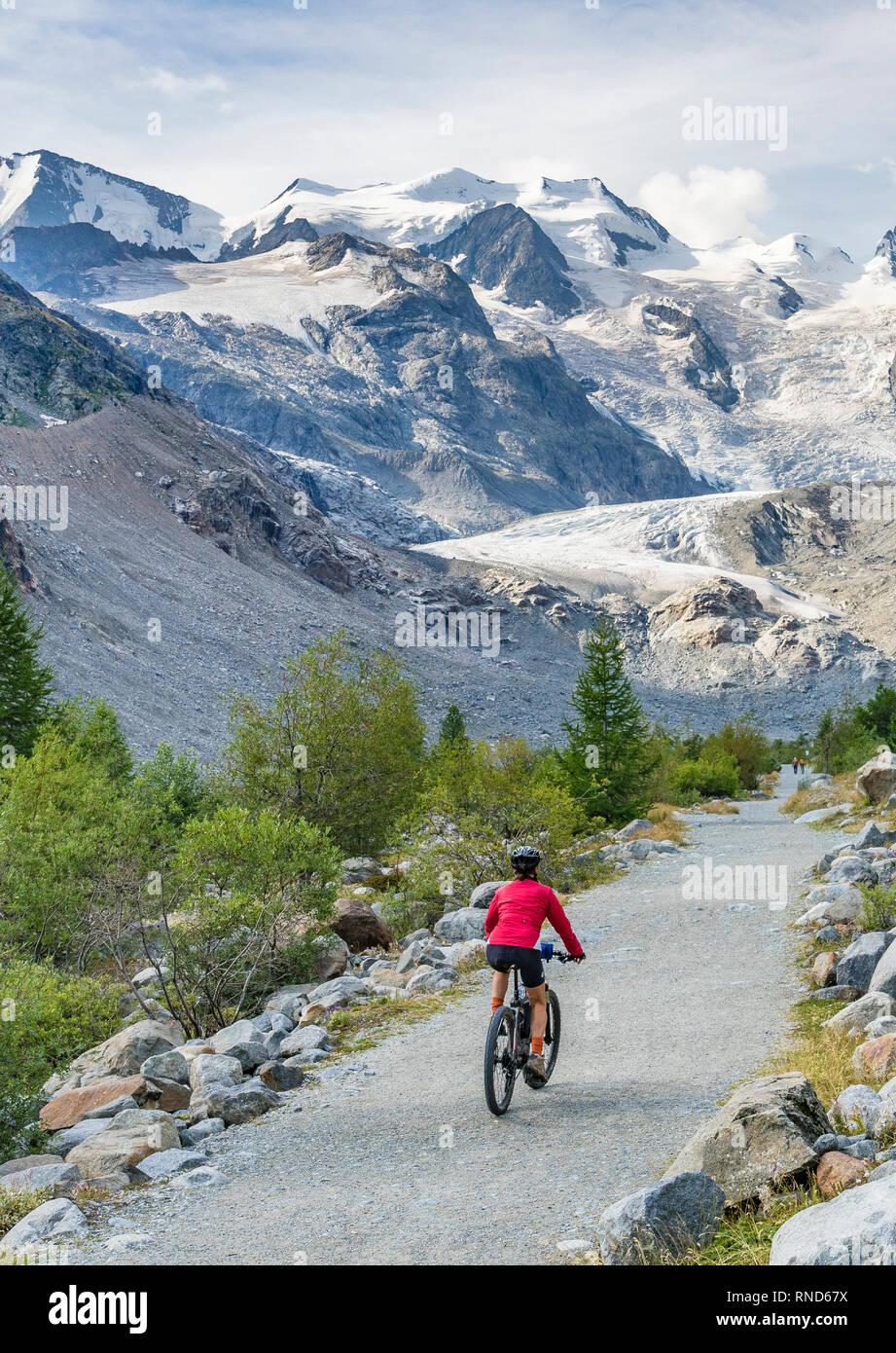 Senior woman, riding her e-mountain bike on the trail to the Morteratsch glacier near Pontresina , Engadin, Switzerland,Alps. - Stock Image