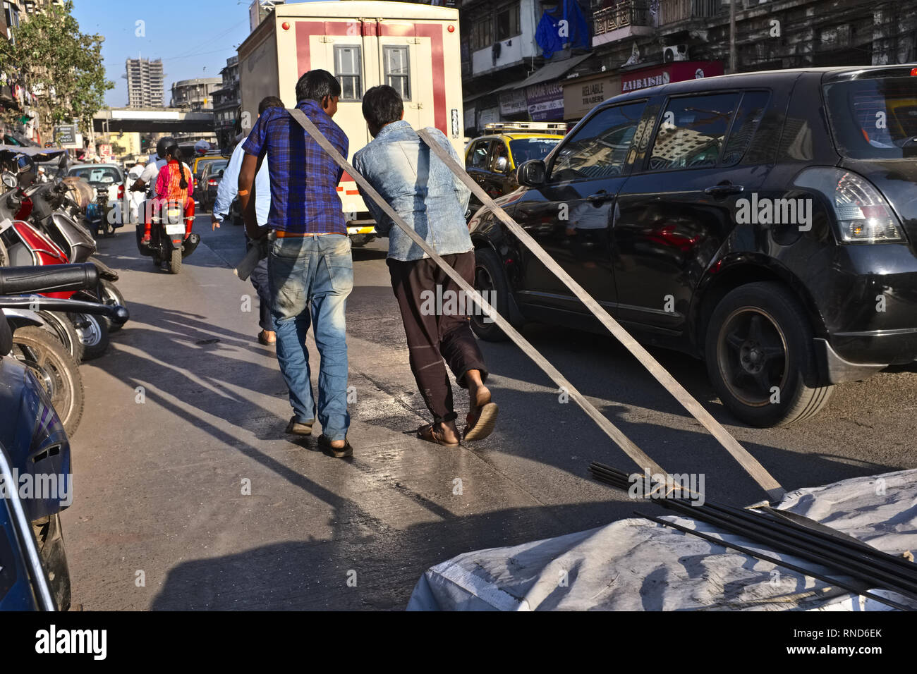 Load carriers pulling a cart with heavy metal sheets on a delivery run in Bhendi Bazar area in Mumbai, India - Stock Image
