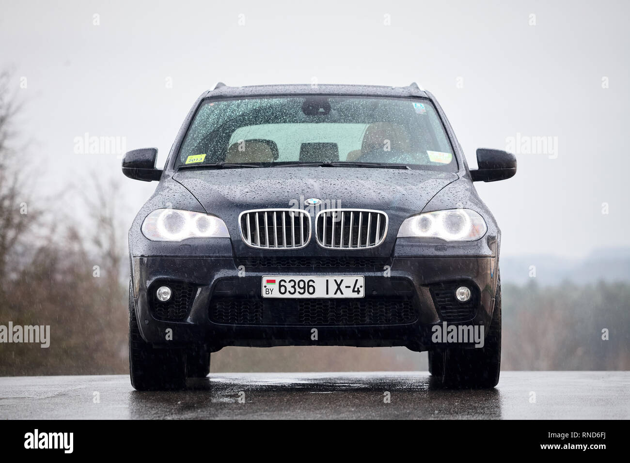 GRODNO, BELARUS - OCTOBER 2016: BMW X5 with glowing headlights standing on asphalt under rain covered with raindrops over gray rainy sky and forest ba - Stock Image