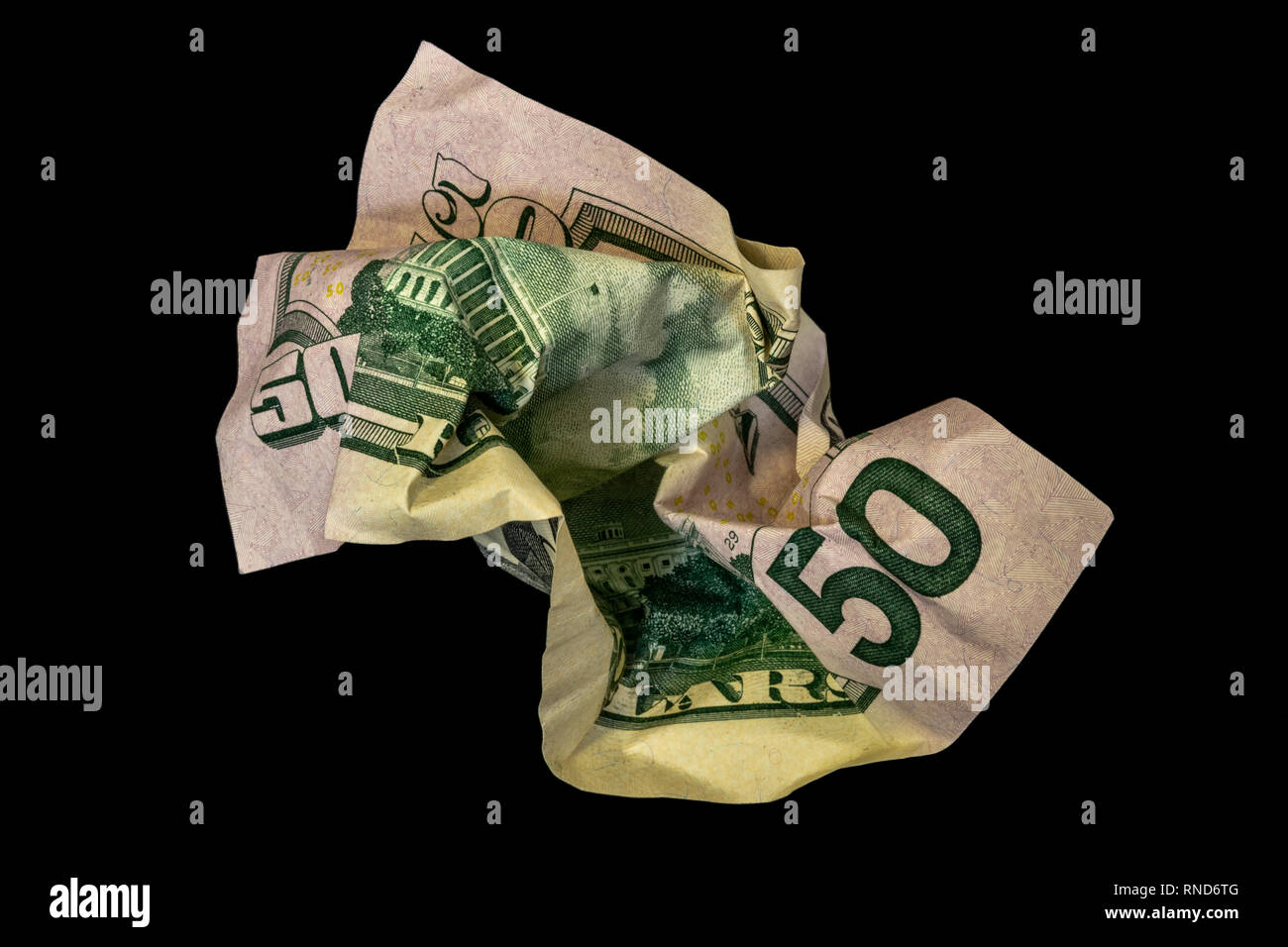 Crumpled fifty dollar bill isolated on black background - Stock Image