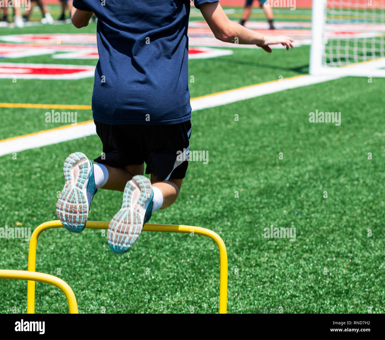 A young kid is jumping over tow foot high yellow mini hurdles at a track and speed camp on a green turf field over the summer. - Stock Image