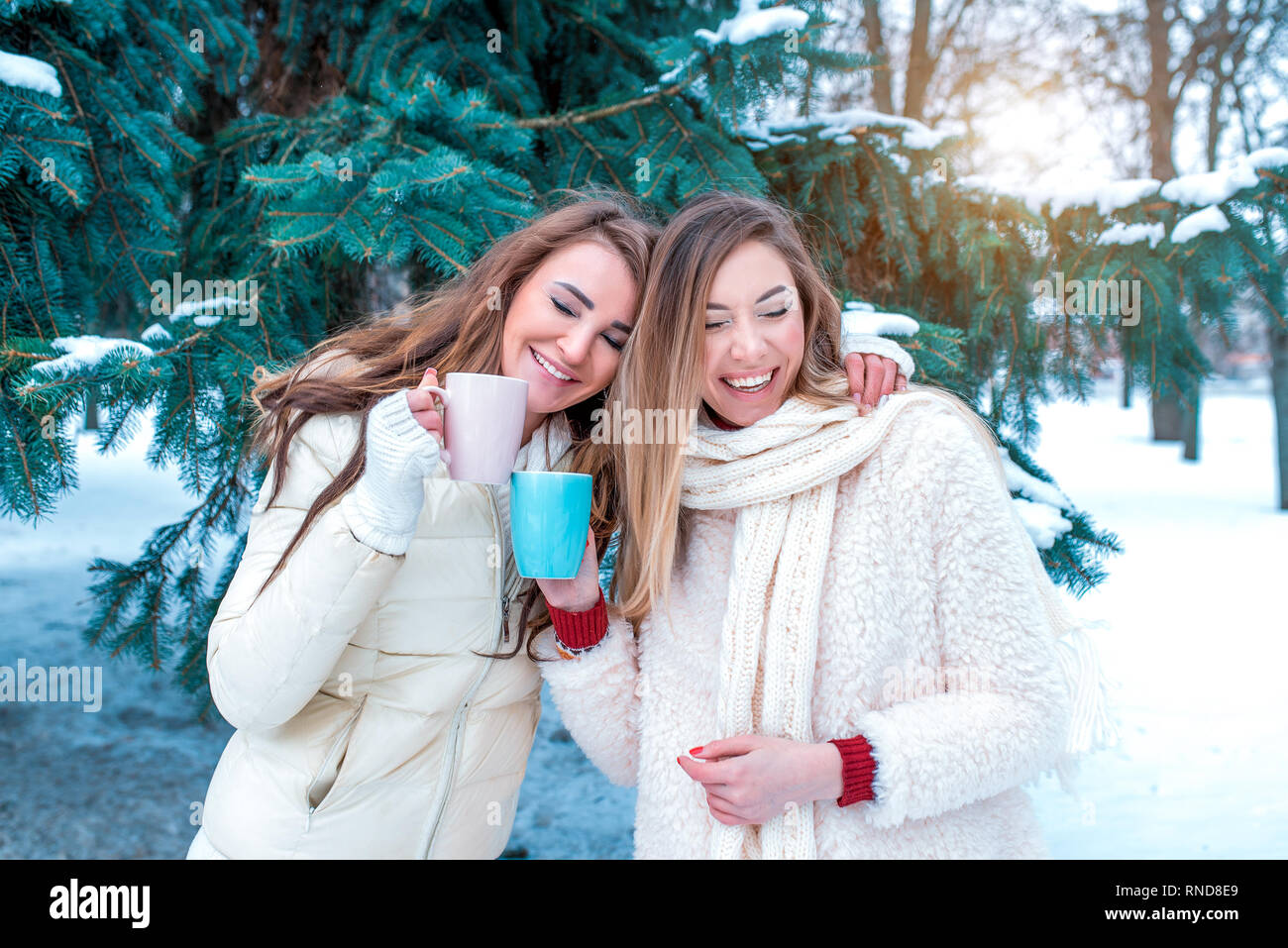 Two girls girlfriends beautiful women happy laugh smiling. Having fun outdoors in winter against backdrop of the Christmas tree. In the hands of mugs - Stock Image
