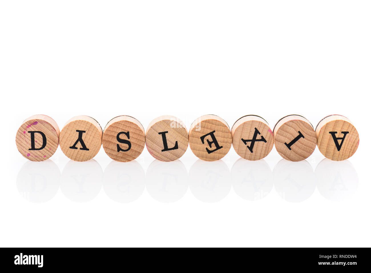 Word Dyslexia from circular wooden tiles with letters children toy. Concept of learning difficulty disorder spelled in children toy letters. - Stock Image