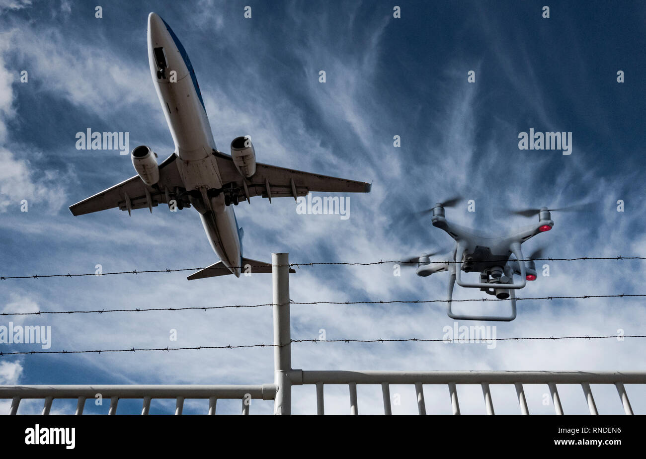Drone flying over airport perimeter fence as airplane takes off. - Stock Image