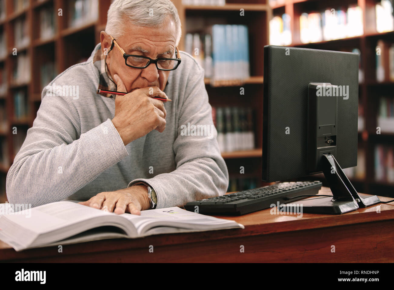 Senior man sitting in a classroom and reading a book. Elderly man sitting in classroom and learning with a book and computer on the table. Stock Photo