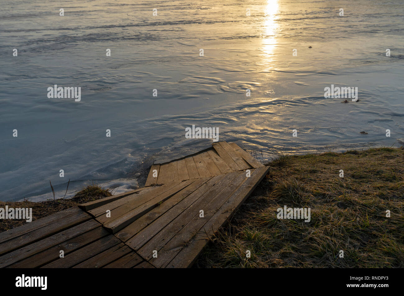 Boardwalk at the edge of a lake at sunset with reflection of the sun on the water and a thin layer of winter ice on the surface in a low angle view - Stock Image