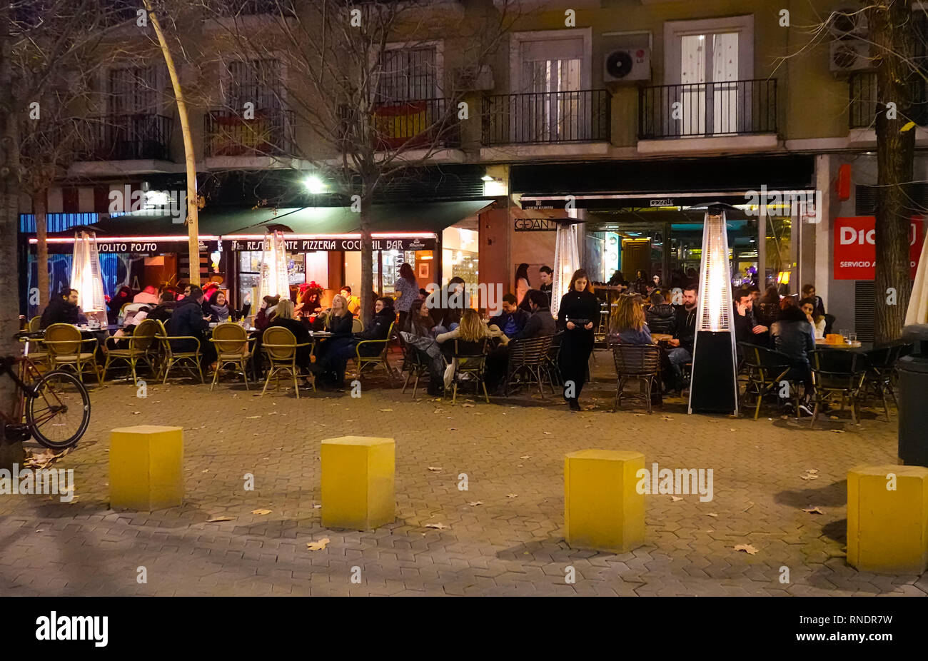 People having food and drinks at an outdoor​ cafe in the Alameda de Hercules in Seville, Spain - Stock Image