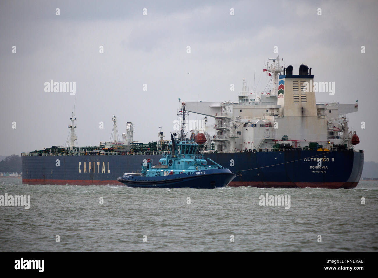 Tug, Tanker, heavily, laden, oil, maneuver, maneuvering, The Solent, Southampton, Fawley, refinery, Isle of Wight, Hampshire, England, UK, - Stock Image