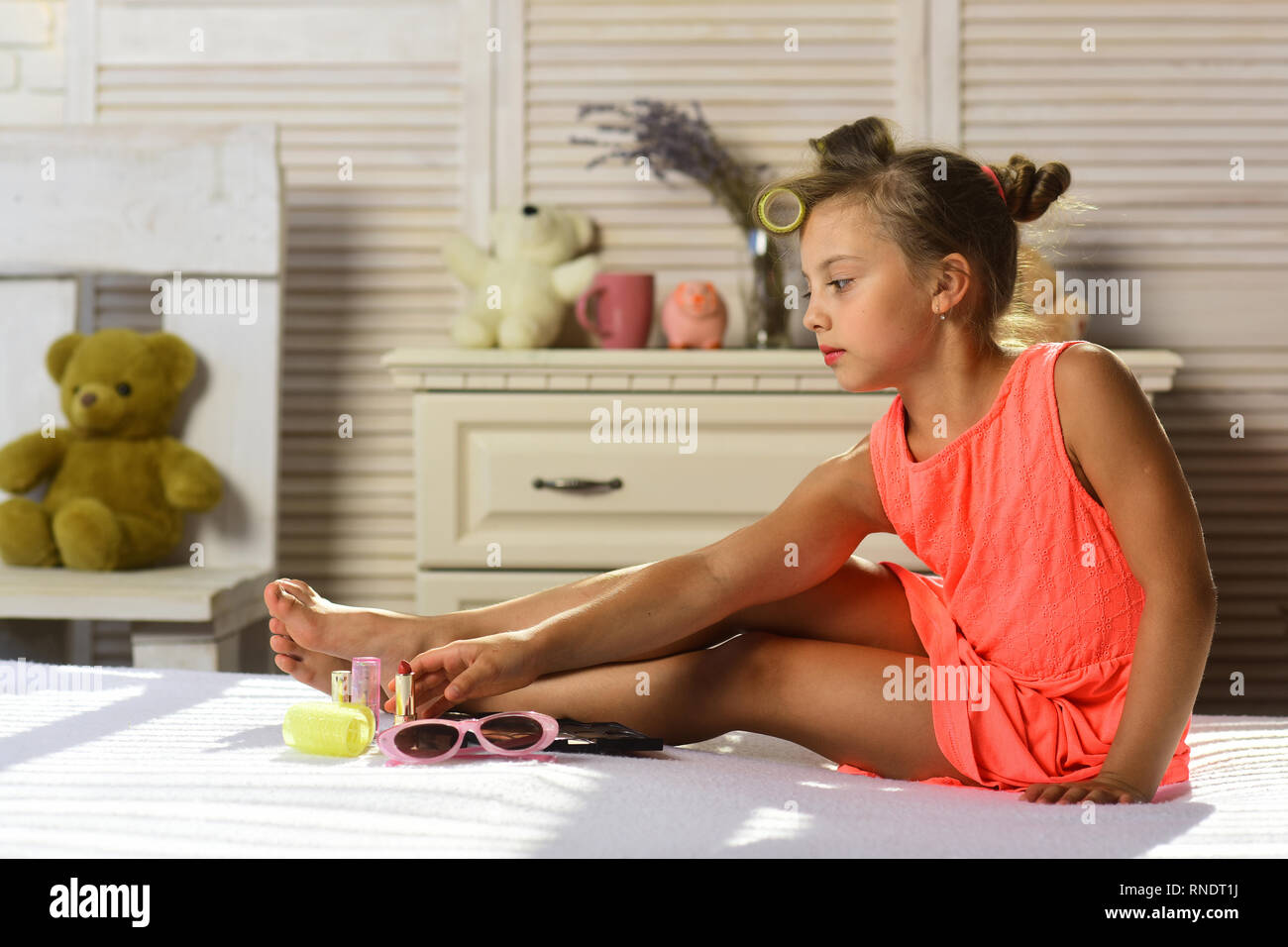 Kid with calm face and makeup accessories in childroom - Stock Image