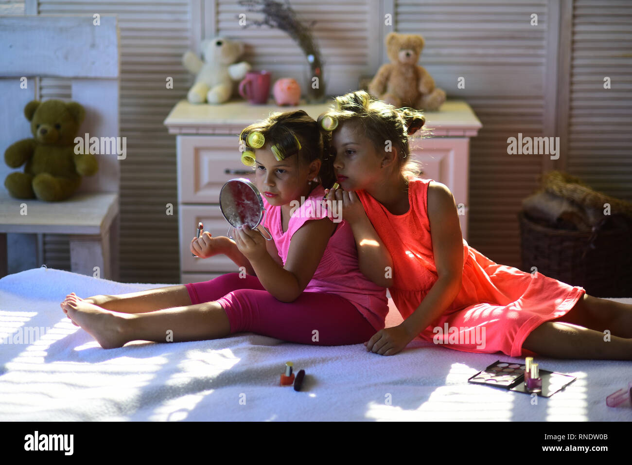 Little girls do makeup sitting in room with toys - Stock Image