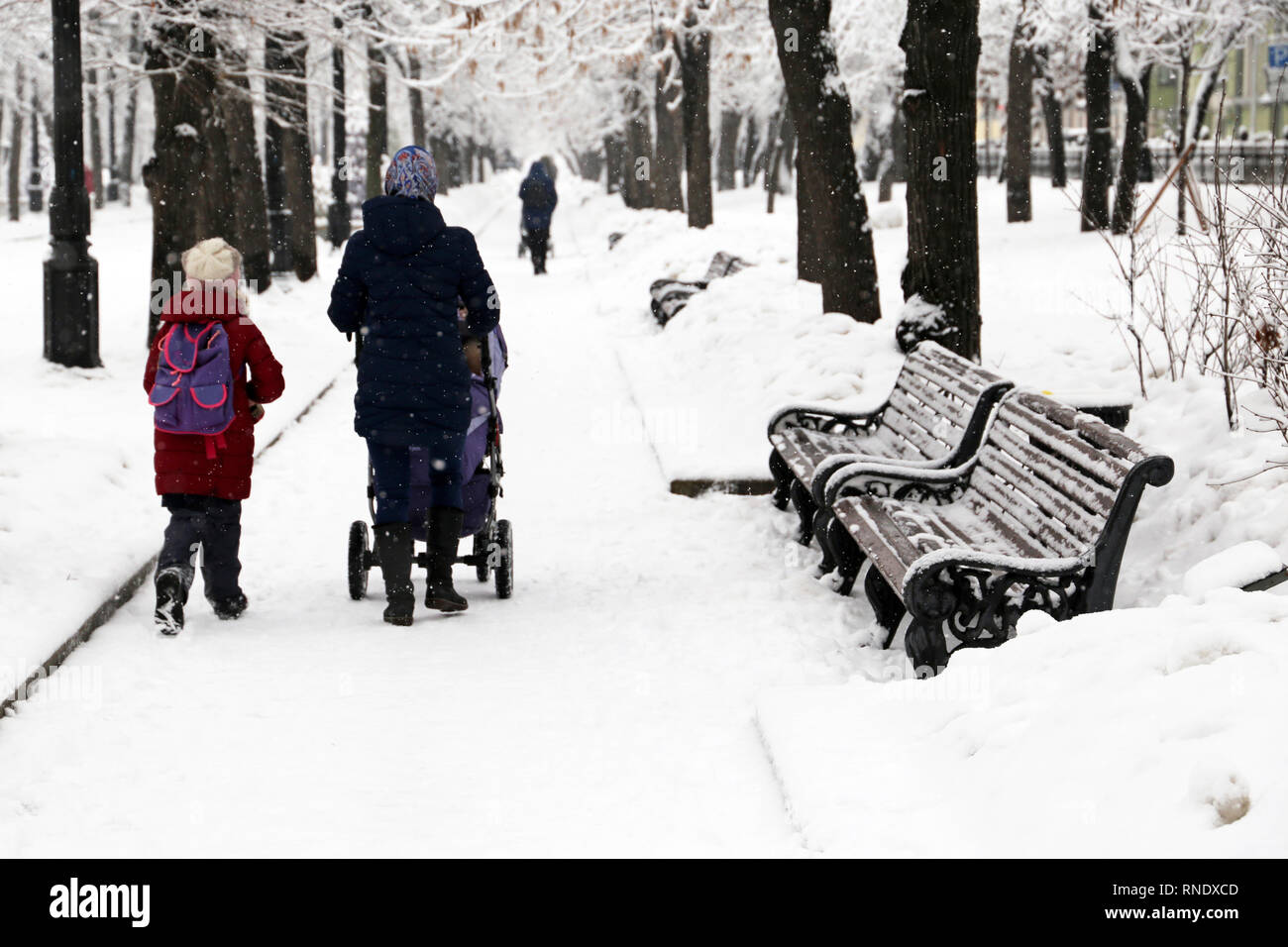 Mom with a stroller and a little daughter walking in the winter park during the snowfall. Going to school, snow weather, single mother - Stock Image
