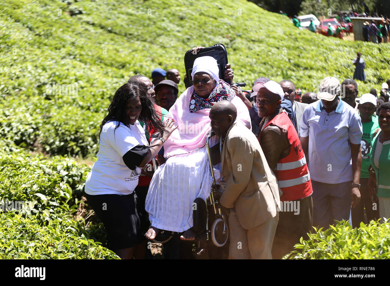 Nyeri, Kenya. 18th Feb, 2019. People seen helping Mukami Kimathi, widow to Kenya's freedom fighter Dedan Kimathi get to a shrine where he was captured in 1956 during the commemoration.Kenya's freedom fighters against British colonial rule called ''˜Mau Mau' commemorated the execution of their leader Dedan Kimathi on February 18, 1957. His body was buried at an unknown grave, widow Mukami Kimathi wants his grave disclosed and remains exhumed for a decent burial. Credit: Billy Mutai/SOPA Images/ZUMA Wire/Alamy Live News - Stock Image