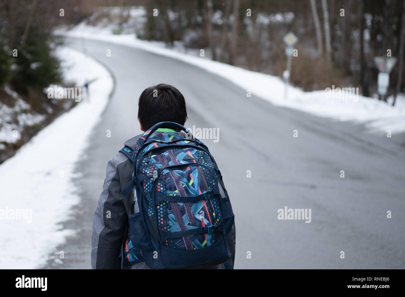 Marktschorgast, Germany. 12th Feb, 2019. Marc walks along a winding country road. The stepfather of the 13-year-old boy had complained that he had to walk about two kilometres to the bus stop of his school bus - over an unlit winding road that leads through a forest and has no sidewalk. In winter, the county pays him a taxi - but not in summer. (to dpa 'On foot over country road without sidewalk - who pays for Marc's way to school?') Credit: Nicolas Armer/dpa/Alamy Live News - Stock Image