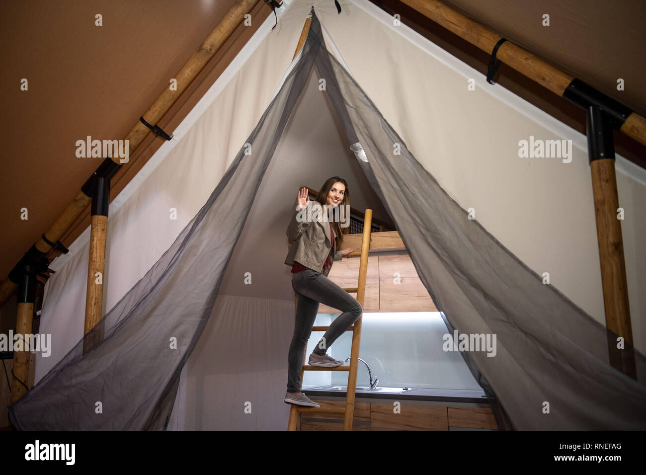 Essen, Germany. 19th Feb, 2019. Model Vivienne climbs up the ladder to the bed in a Daalmann mobile home safari tent. Based on the classic design of the former safari tent, it offers a modular structure and state-of-the-art technology. The fair will take place from 20 to 24 February. Credit: Bernd Thissen/dpa/Alamy Live News - Stock Image