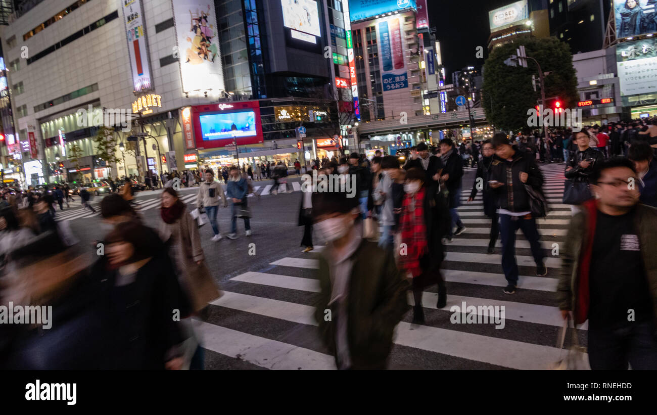 TOKYO, JAPAN - DECEMBER 23, 2012: Pedestrians cross at Shibuya Crossing. It is one of the world's most famous and busiest scramble crosswalks in the w - Stock Image