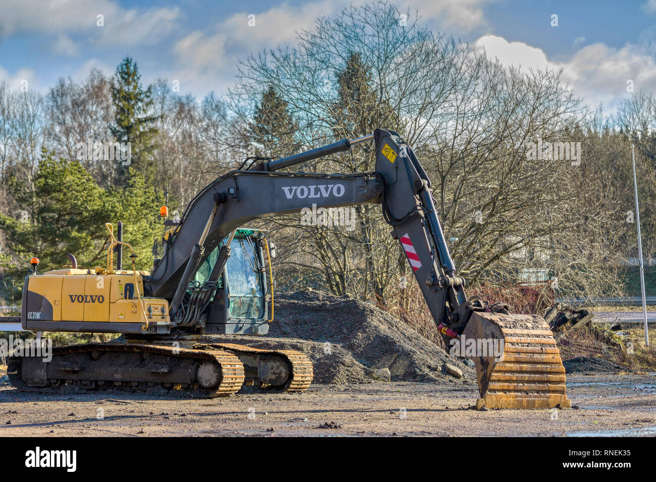 Sideview of stationary and parked Volvo EC210C crawler excavator outdoors - Stock Image