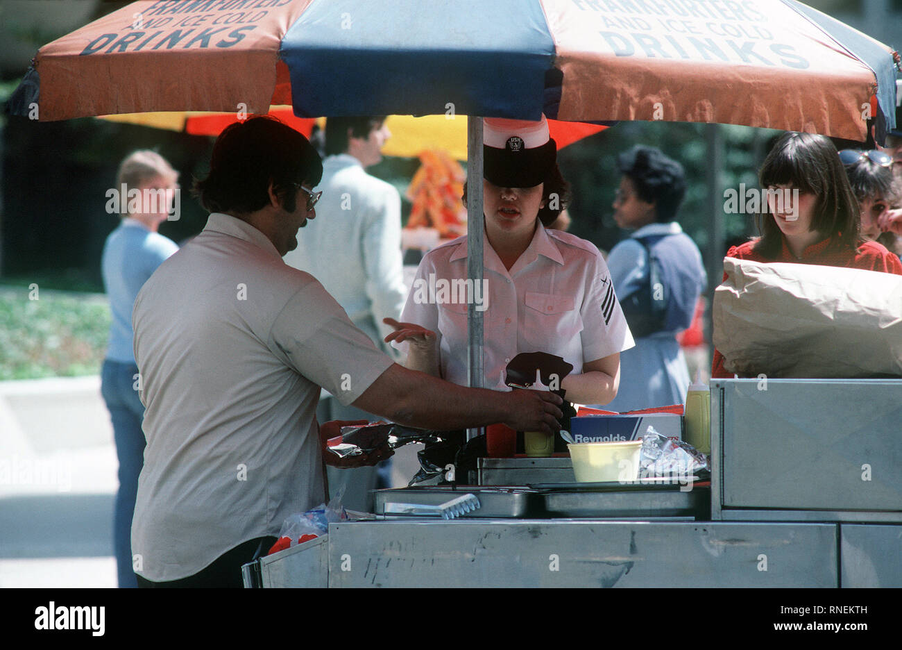 1982 - A Navy woman takes her lunch break at a hot dog stand in Crystal City. - Stock Image