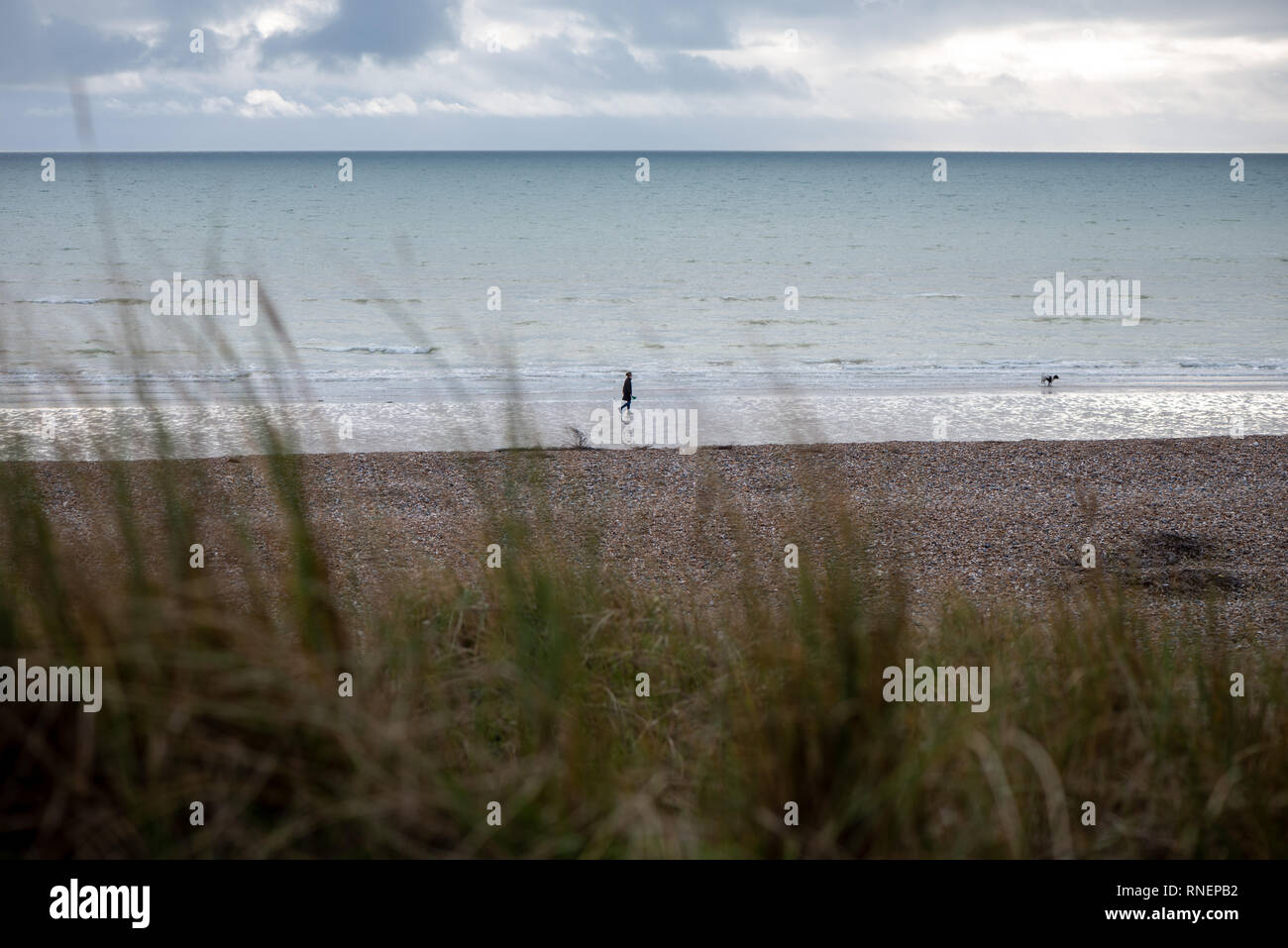 A lone person walks a dog along a deserted beach against a dramatic sky on a winters day. West Beach, Littlehampton, West Sussex, UK. - Stock Image